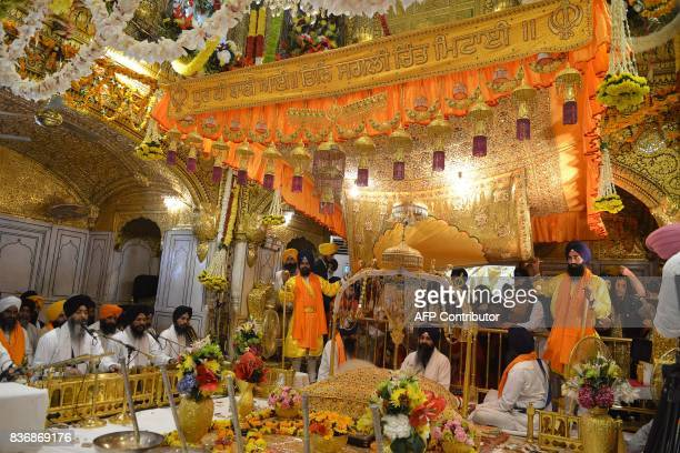 Indian Sikh priest Gurminder Singh sits behind the Sikh Holy Book the Guru Granth Sahib during a 'Jalau' a splendour show of Sikhism's symbolic items...