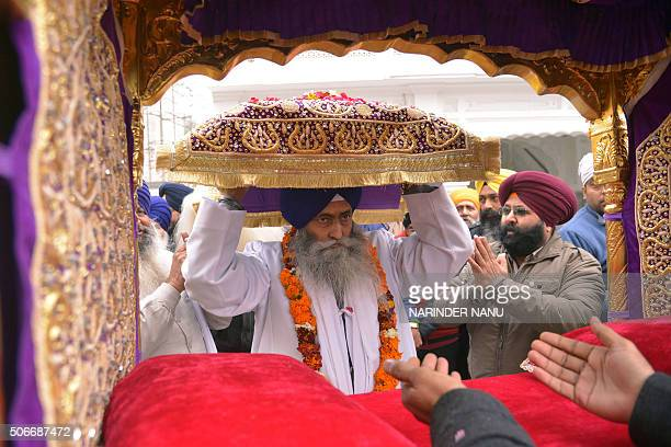 Indian Sikh priest Jagtar Singh places the Sikh Holy Book Guru Granth Sahib in a Palki Sahib during a procession at the Golden Temple in Amritsar on...