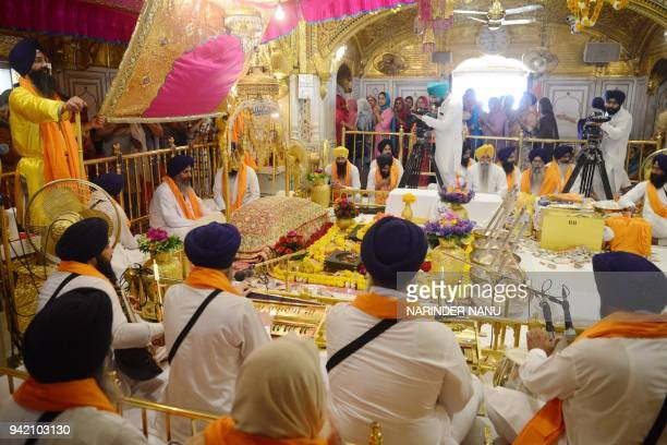 Indian Sikh priest Maan Singh sits behind the Guru Granth Sahib during a 'Jalau' splendour show of Sikhism's symbolic items on the 397th anniversary...