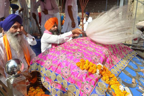 Indian Sikh priest sits behind the Palki Sahib in which the Guru Granth Sahib the Sikh Holy book is placed during a procession to mark Guru Nanak...