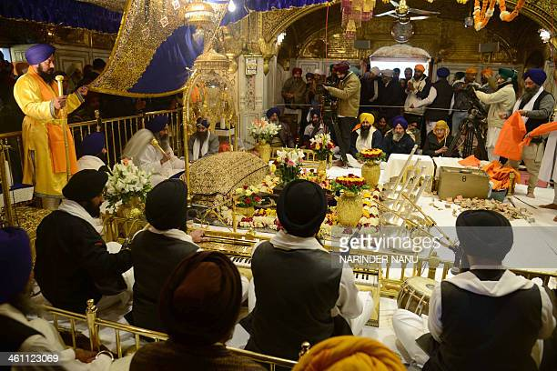 Indian Sikh priest Sukhjinder Singh sits behind the Sikh Holy Book Guru Granth Sahib as Sikhism's symbolic items are displayed inside the Golden...