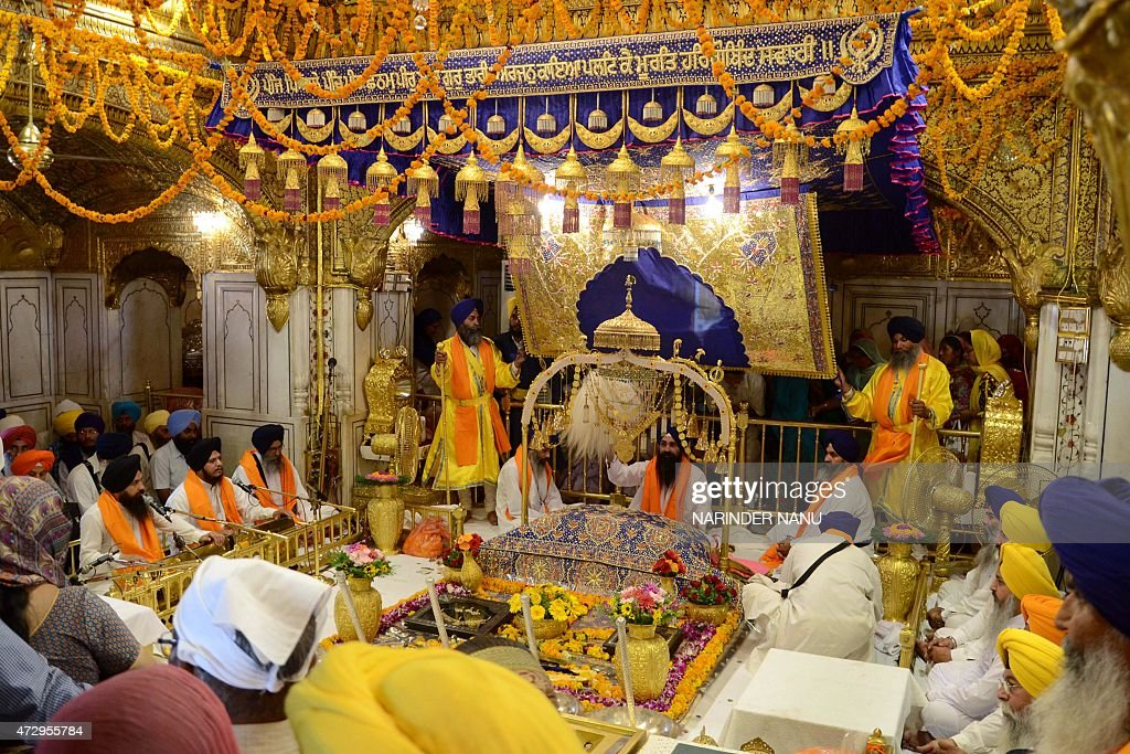 Indian Sikh priests sit behind the Guru Granth Sahib during a `Jalau` a splendour show of Sikhism`s symbolic items inside the Golden Temple in...