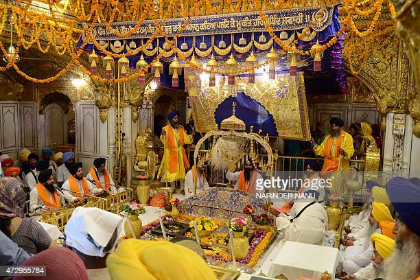 Indian Sikh priests sit behind the Guru Granth Sahib during a 'Jalau' a splendour show of Sikhism's symbolic items inside the Golden Temple in...