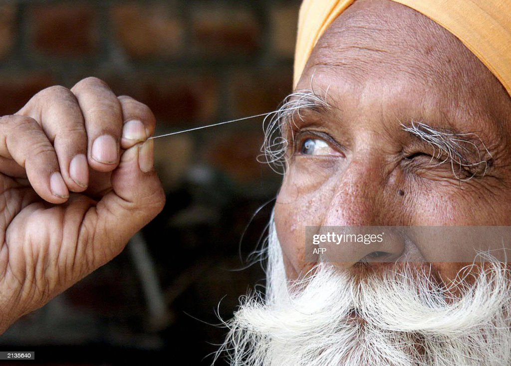 Indian Sikh Sardar Pishora Singh displays his 9 cm long eyebrow hair to the press in Amritsar 03 July 2003 Singh who has been growing his eyebrow...
