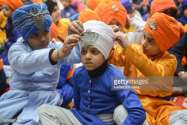 Indian Sikh school boys adjust the turban of a friend at an event at the start of a week to mark Sahibzade in memory of the killing of the songs of...