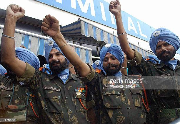 Indian Sikh soldiers of 15 Sikh Light Infantary fist salute at the Indira Ganghi International airport in New Delhi 16 July 2003 before their...