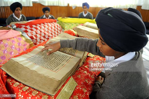 Indian Sikh students pose by copies of the 350year old Sikh holy Book Guru Granth Sahib at the Gurmati Sangeet Workshop exhibition in Amritsar on...