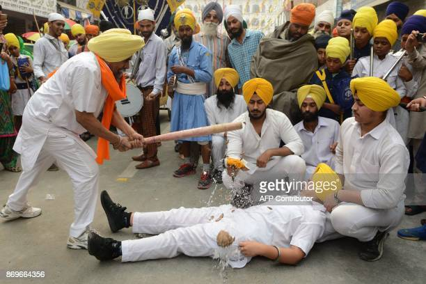 Indian Sikh youth perform the Sikh martial art known as 'Gatka' where a baseball bat is used to break a coconut on the performer's crotch during a...