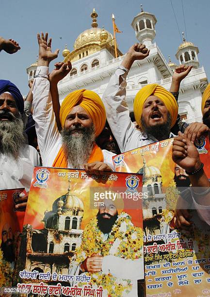 Indian Sikhs hold posters showing the demolished Akal Takht, and Bhai Amrik Singh, who was killed during Operation Bluestar in 1984, as they shout...