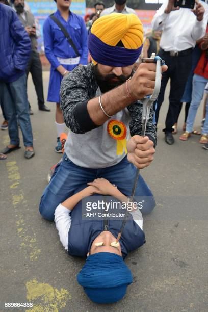 Indian Sikhs perform the Sikh martial art known as Gatka where the blindfolded man uses a sword to skewer items resting on another performer's eyes...