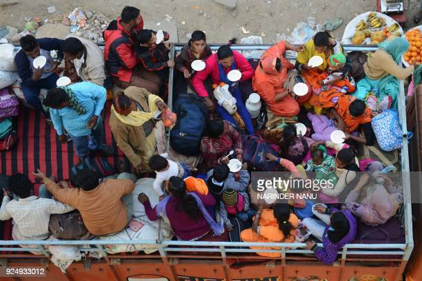Indian Sikhs sit on the top of a truck as they prepare to travel to Anandpur Sahib for the upcoming Hola Mohalla festival in Amritsar on February 27...