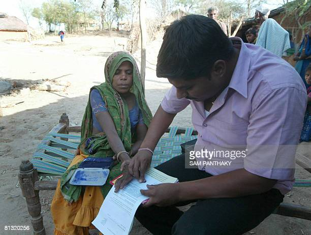 Indian silicotuberculosis sufferer Menaben Nandubhai Damor is assisted by Peoples Training & Research Centre official Sanket Mali as she signs a...