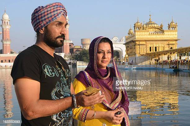 Indian singer and actor Jassi Jasraj along with film producer Prabhjot Kaur pose at the Golden Temple in Amritsar on March 8 2013 The actors visited...