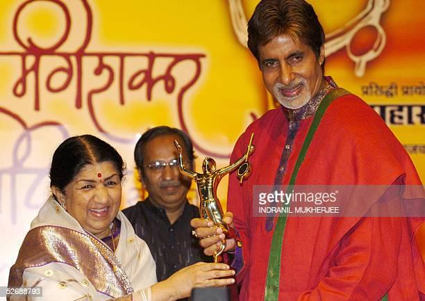 Indian singer Lata Mangeshkar laughs as she presents the annual Pundit Dinanath Mangeshkar Memorial award to Indian filmstar Amitabh Bachchan in...