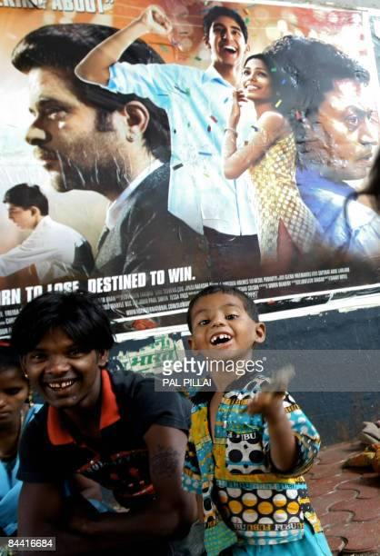 Indian slum children play in front of a poster of the Oscar nominated film 'Slumdog Millionaire' in Mumbai on January 23 2008 'Slumdog Millionaire'...