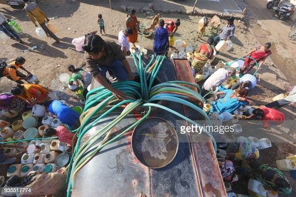 TOPSHOT Indian slum dwellers collect potable water from a municipal water tanker in Durga Nagar area of Bhopal on March 21 2018 Slum dwellers depend...