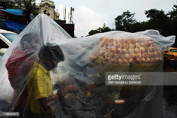 Indian snack vendors stand underneath a translucent tarp offering protection from the monsoon rains as they wait for customers by a roadside in...