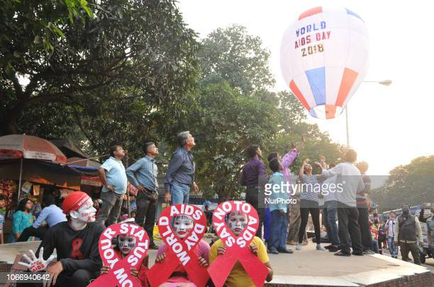 Indian social activists and children hold Poster and release a World AIDS Day awareness sign tied with Fanush or sky lantern to create awareness...