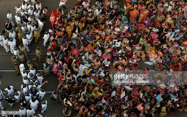 Indian social activists shout slogans as they gather on a road penned in by police officers following the judgment in the Kamduni rape and murder...