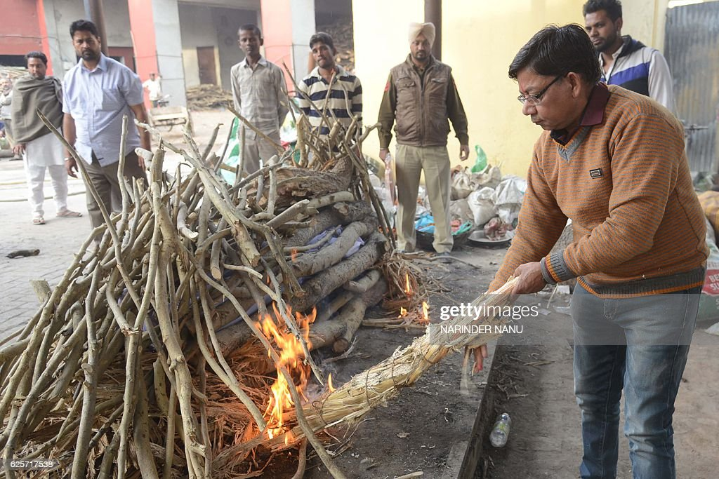 Indian social worker BK Sharma lights the funeral pyre of an unidentified person at a cremation ground in Amritsar on November 25 2016 Sharma has...