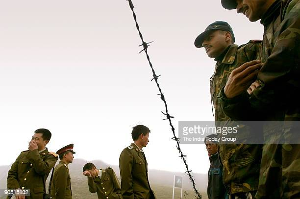 Indian soldiers and Chinese soldiers stand on either side of barbed wire on the border fence at Nathu La Trade between India and China is set to...