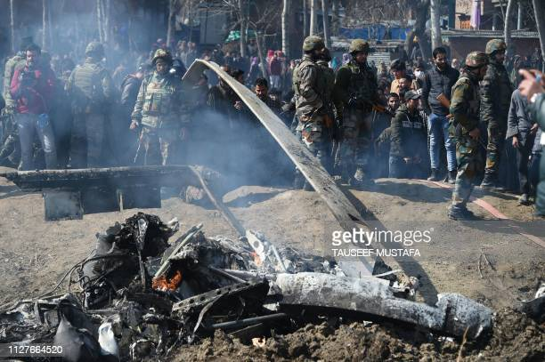 Indian soldiers and Kashmiri onlookers stand near the remains of an Indian Air Force helicopter after it crashed in Budgam district outside Srinagar...