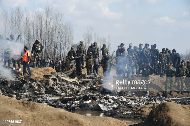 Indian soldiers and Kashmiri onlookers stand near the remains of an Indian Air Force helicopter after it crashed in Budgam district on the outskirts...
