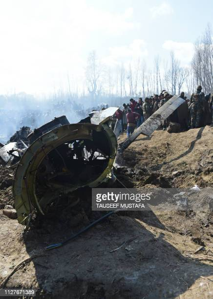 Indian soldiers and Kashmiri onlookers stand near the remains of an Indian Air Force helicopter after it crashed in Budgam district, outside Srinagar...
