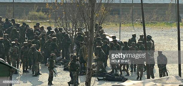 Indian soldiers are seen gathered over the bodies of suspected militants following an attack on an army barracks in Gingal Uri some 90 kms north of...