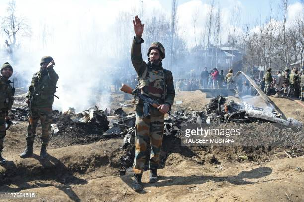 Indian soldiers gesture near the remains of an Indian Air Force helicopter after it crashed in Budgam district outside Srinagar on February 27 2019...