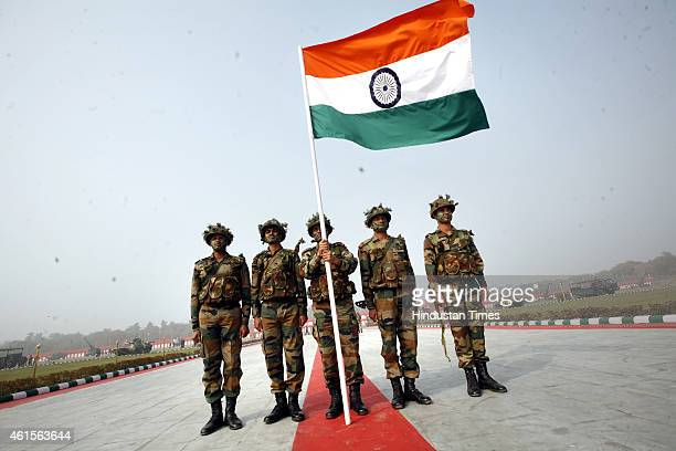 Indian soldiers hold up their national flag as they demonstrate combat skills during the Army Day parade at Delhi Cantt on January 15 2015 in New...