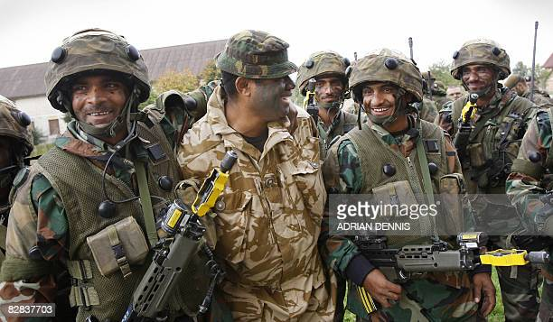 Indian soldiers hug a British soldier following an exercise during joint training with the British Army at Copehill Down military training village on...