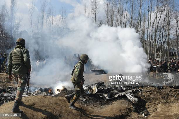 Indian soldiers inspect the remains of an Indian Air Force helicopter after it crashed in Budgam district outside Srinagar on February 27 2019...