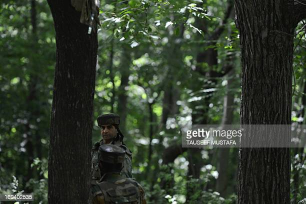 Indian soldiers keep watch from their position as a gunbattle with suspected armed rebels rages on a few kilometers away in the village of Hardu...