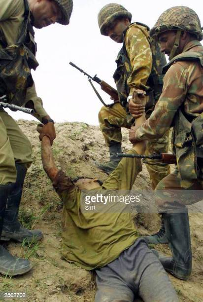 Indian soldiers of the Border Security Force drag a body of an alledged militant in Alfa Manchal Chackorli Jammu 23 September 2003 Seventeen more...