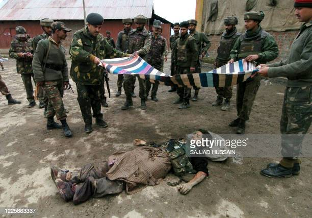 Indian soldiers prepare to cover the body of an alledged militant after an encounter with Muslim rebels at Pampore, some 15 kms south of Srinagar, 26...