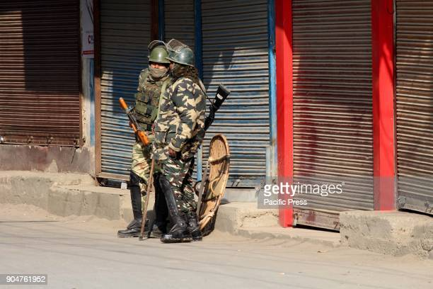 Indian soldiers stand guard in front of close shops to prevent protest due to a strike call issued by the Joint Resistance Leadership against...