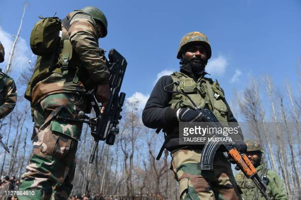 Indian soldiers stand guard near the remains of an Indian Air Force helicopter after it crashed in Budgam district on the outskirts of Srinagar on...