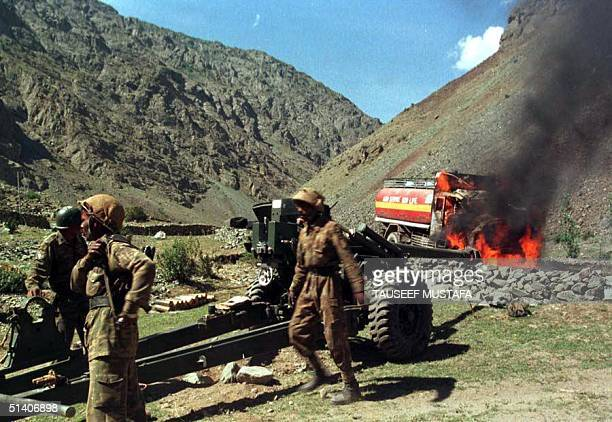 Indian soldiers struggle to move an artillery piece after an oil tanker was set ablaze by shrapnel from a Pakistani shell near the village of Kharbu...