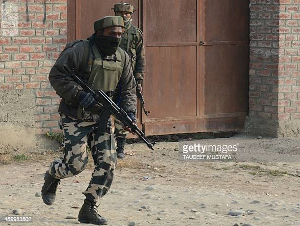 Indian soldiers take positions during a gunfight with suspected rebels on the outskirts of Srinagar on December 5 2014 Militants hurling grenades...