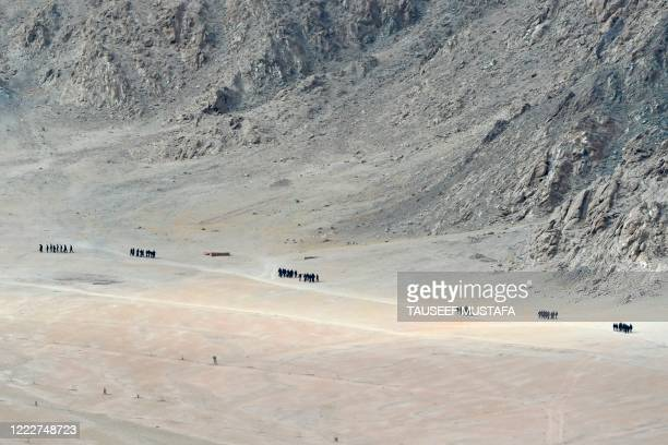 Indian soldiers walk at the foothills of a mountain range near Leh, the joint capital of the union territory of Ladakh, on June 25, 2020. - Indian...