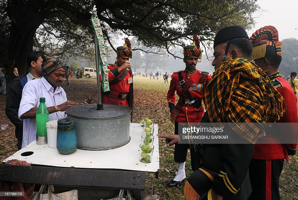 Indian soldiers watch a street vendor prepare a drink as