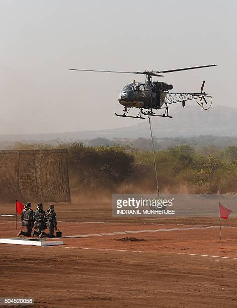 Indian soldiers watch as a 120mm Brandt Mortar is lowered from a Cheetah helicopter during Exercise Sarvatra Prahar at the School of Artillery in...