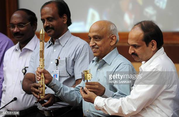 Indian Space Research Organisation chairman Kiran Kumar Rao along with members of the team gestures as he displays models of the ISRO's CARTOSAT2 and...