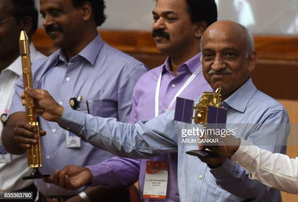 Indian Space Research Organisation chairman Kiran Kumar Rao displays models of the CARTOSAT2 and Polar Satellite Launch Vehicle as he speaks to media...