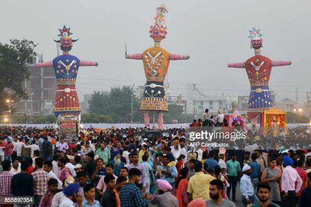 Indian spectators gather around effigies of the Hindu demon king Ravana and his son Meghnath and brother Kumbhkar before they are set alight in...