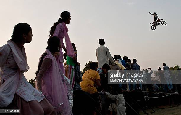 Indian spectators watch as a Freestyle Motocross RedBull XFighters rider perform at the India Gate in New Delhi on June 30 2012 Three of the top ten...