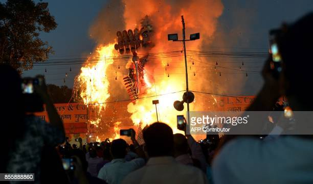 Indian spectators watch the burning of the effigy of the Hindu demon Ravana stuffed with firecrackers at an event marking the Hindu festival of...