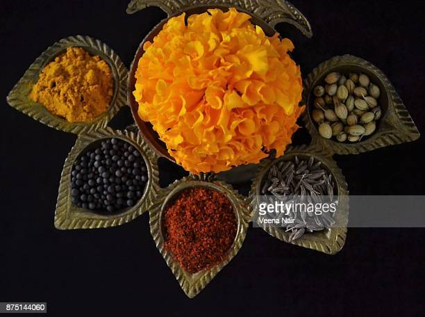 Indian spices and marigold flower arranged in a five wick brass lamp