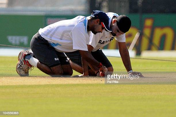 Indian spin bowlers Amit Mishra and Harbhajan Singh have a closer look at the pitch during an Indian Nets Session at Punjab Cricket Association...